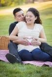 Έγκυο ισπανικό ζεύγος που κάνει τη μορφή καρδιών με τα χέρια στην κοιλιά Στοκ Φωτογραφία