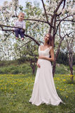 Έγκυο κορίτσι με μακρυμάλλη φορώντας ένα άσπρο φόρεμα που στέκεται το γιο του στο δέντρο Στοκ Φωτογραφίες