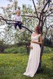 Έγκυο κορίτσι με μακρυμάλλη φορώντας ένα άσπρο φόρεμα που στέκεται το γιο του στο δέντρο Στοκ Εικόνες
