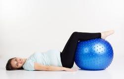 Έγκυο κορίτσι που βρίσκεται στο fitball Στοκ Φωτογραφία