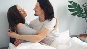 Έγκυο κορίτσι που δίνει τη δοκιμή εγκυμοσύνης τύπων, αγκάλιασμα φιλήματος ζευγών στο κρεβάτι στο σπίτι απόθεμα βίντεο