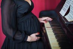 Έγκυο κορίτσι σε ένα μαύρο πιάνο παιχνιδιών φορεμάτων Στοκ Φωτογραφία