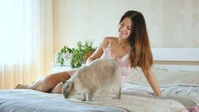 Έγκυο παιχνίδι κοριτσιών με μια γάτα Η γυναίκα κτυπά το κατοικίδιο ζώο Γάτα στο κρεβάτι κοντά στην κυρία της απόθεμα βίντεο