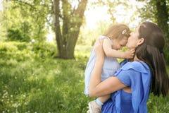 Έγκυο παιχνίδι μητέρων με λίγη κόρη στο πάρκο στοκ φωτογραφία
