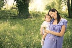 Έγκυο παιχνίδι μητέρων με λίγη κόρη στο πάρκο Στοκ Εικόνες