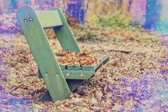 Έδρα στο πάρκο κάτω από τα φύλλα με την επίδραση φλογών φακών Εκλεκτής ποιότητας τόνος στοκ φωτογραφία με δικαίωμα ελεύθερης χρήσης