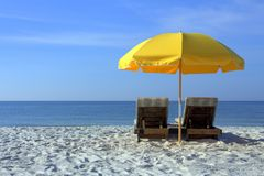 Έδρες παραλιών με την κίτρινη ομπρέλα στην άσπρη αμμώδη παραλία στοκ φωτογραφία