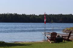 Έδρες που κοιτάζουν πέρα από την όμορφη άποψη λιμνών με τη σημαία του Καναδά στοκ εικόνα με δικαίωμα ελεύθερης χρήσης