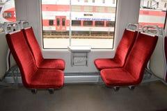 Έδρες σε ένα ηλεκτρικό τραίνο με την κόκκινη ταπετσαρία velor Το εσωτερικό του αυτοκινήτου τραίνων στοκ φωτογραφία