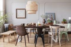 Έδρες στον ξύλινο να δειπνήσει πίνακα κάτω από το λαμπτήρα στο εσωτερικό τραπεζαρίας με τις αφίσες και τα λουλούδια Πραγματική φω στοκ φωτογραφία με δικαίωμα ελεύθερης χρήσης