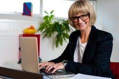 Έκθεση δακτυλογράφησης διευθυντών χαμόγελου θηλυκή σχετικά με το lap-top Στοκ Φωτογραφία