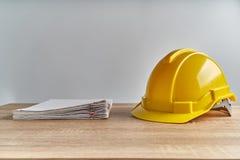 Έκθεση εγγράφων σωρών με το κίτρινο καπέλο μηχανικών σχετικά με τον ξύλινο πίνακα στοκ φωτογραφία