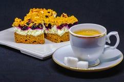 Έκθεση του κέικ με την άσπρη κρέμα Aronia στο άσπρο πιάτο κοντά στο φλιτζάνι του καφέ με τη ζάχαρη που απομονώνεται στο μαύρο υπό Στοκ Φωτογραφίες