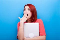 Έκπληκτη γυναίκα που καλύπτει το στόμα της κρατώντας ένα lap-top σε την Στοκ Εικόνες