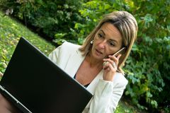 Έκπληκτη επιχειρηματίας που μιλά στο τηλέφωνο κυττάρων χρησιμοποιώντας το lap-top στη φύση Στοκ Εικόνες