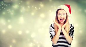 Έκπληκτη νέα γυναίκα με την τοποθέτηση καπέλων Santa Στοκ Φωτογραφίες