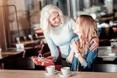 Έκπληκτη νέα γυναίκα που παίρνει ένα όμορφο παρόν από την αγαπώντας γιαγιά της στοκ εικόνες με δικαίωμα ελεύθερης χρήσης