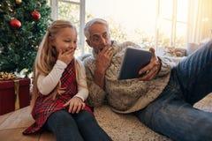 Έκπληκτοι παππούς και εγγονή που εξετάζουν τον ψηφιακό πίνακα Στοκ φωτογραφία με δικαίωμα ελεύθερης χρήσης