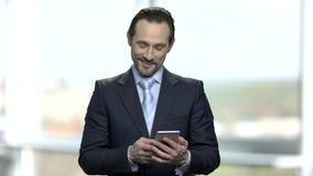 Έκπληκτος επιχειρηματίας που εξετάζει το smartphone του φιλμ μικρού μήκους