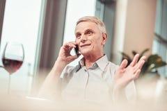 Έκπληκτος συνταξιούχος που έχει μια συνομιλία στο τηλέφωνο στοκ φωτογραφίες
