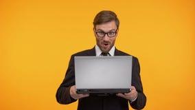 Έκπληκτο άτομο που διαβάζει τις καλές ειδήσεις στο lap-top, ψωνίζοντας on-line, πώληση καταστημάτων Διαδικτύου απόθεμα βίντεο