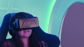 Έκπληκτο κορίτσι που δοκιμάζει την εικονική πραγματικότητα σε μια κινούμενη διαλογική καρέκλα Στοκ φωτογραφία με δικαίωμα ελεύθερης χρήσης