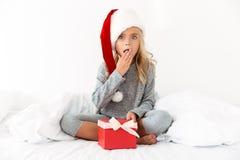 Έκπληκτο μικρό κορίτσι στο καπέλο Santa ` s που κρατά παρόν ενώ sittin Στοκ Φωτογραφία