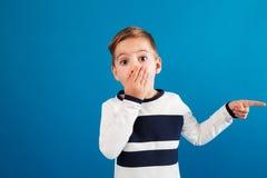 Έκπληκτο νέο αγόρι στο πουλόβερ που δείχνει μακριά και που καλύπτει το στόμα στοκ φωτογραφίες με δικαίωμα ελεύθερης χρήσης