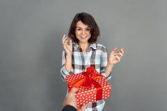 Έκπληξη εορτασμού Δόσιμο ανδρών παρόν στη γυναίκα που απομονώνεται στο γκρίζο χαμόγελο έκπληκτο στοκ φωτογραφία με δικαίωμα ελεύθερης χρήσης
