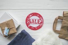 Έκπτωση στα στοιχεία στο άσπρο ξύλινο υπόβαθρο στο ύφος τζιν με την κόκκινη ετικέτα Στοκ φωτογραφία με δικαίωμα ελεύθερης χρήσης