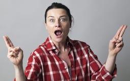 Έκπληκτη γυναίκα που παρουσιάζει δάχτυλα όπως τα πυροβόλα όπλα διασκέδασης για τη θηλυκή δύναμη Στοκ εικόνες με δικαίωμα ελεύθερης χρήσης