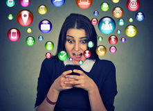 Έκπληκτη γυναίκα που χρησιμοποιεί τα κοινωνικά εικονίδια μέσων smartphone που πετούν έξω την οθόνη Στοκ φωτογραφία με δικαίωμα ελεύθερης χρήσης