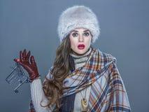 Έκπληκτη γυναίκα στο κρύο μπλε καροτσάκι αγορών εκμετάλλευσης Στοκ Εικόνες
