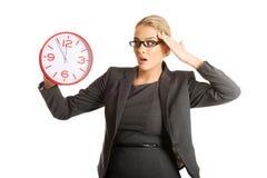 Έκπληκτη επιχειρηματίας που κρατά ένα μεγάλο ρολόι Στοκ εικόνα με δικαίωμα ελεύθερης χρήσης