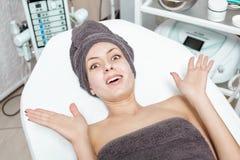Έκπληκτη νέα γυναίκα brunette που περιμένει την επεξεργασία SPA στο σαλόνι SPA cosmetology Στοκ Εικόνα