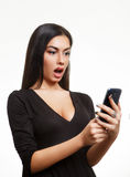 Έκπληκτη συγκλονισμένη γυναίκα που εξετάζει το τηλέφωνο Στοκ φωτογραφία με δικαίωμα ελεύθερης χρήσης