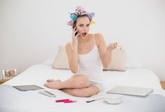 Έκπληκτη φυσική καφετιά μαλλιαρή γυναίκα στα ρόλερ τρίχας που καλούν με το κινητό τηλέφωνό της Στοκ Εικόνες