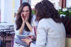 Έκπληκτη brunet εξέταση την ταμπλέτα Στοκ Φωτογραφία