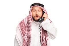 Έκπληκτος Άραβας που κρατά έναν τηλεφωνικό ομιλητή Στοκ Εικόνες