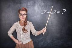 Έκπληκτος δάσκαλος με το δείκτη στο υπόβαθρο πινάκων κιμωλίας Στοκ Εικόνες