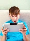 Έκπληκτος έφηβος με μια ταμπλέτα Στοκ Φωτογραφία