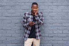 Έκπληκτος νέος αφρικανικός τύπος που εξετάζει το τηλέφωνο κυττάρων Στοκ Εικόνα