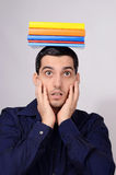Έκπληκτος σπουδαστής που κρατά έναν σωρό των βιβλίων στο κεφάλι του. Στοκ Εικόνες