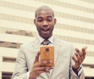 Έκπληκτος όμορφος νεαρός άνδρας που εξετάζει το τηλέφωνο Στοκ φωτογραφία με δικαίωμα ελεύθερης χρήσης