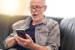 Έκπληκτο άτομο που εξετάζει το τηλέφωνο της Mobil του, ελαφριά επίδραση Στοκ φωτογραφία με δικαίωμα ελεύθερης χρήσης