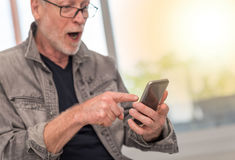 Έκπληκτο άτομο που εξετάζει το τηλέφωνο της Mobil του, ελαφριά επίδραση Στοκ Εικόνα