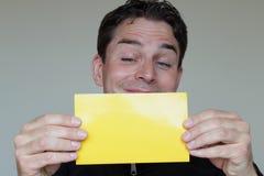 Έκπληκτο άτομο που κρατά ένα κενό έγγραφο για τη διαφήμιση Στοκ Φωτογραφία