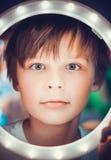 Έκπληκτο αγόρι που εξετάζει τη κάμερα μέσω ενός φωτεινού κύκλου ως αστροναύτης Στοκ φωτογραφία με δικαίωμα ελεύθερης χρήσης