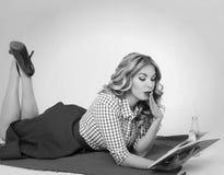 Έκπληκτο κορίτσι με διαθέσιμο έναν αναδρομικό βιβλίων στοκ εικόνες