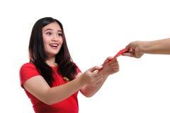 Έκπληκτο κορίτσι που λαμβάνει το angpao που απομονώνεται Στοκ Φωτογραφία